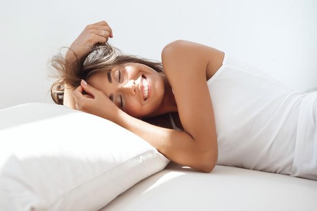 Jonge mooie vrouw liggend op bed vroeg in de ochtend.
