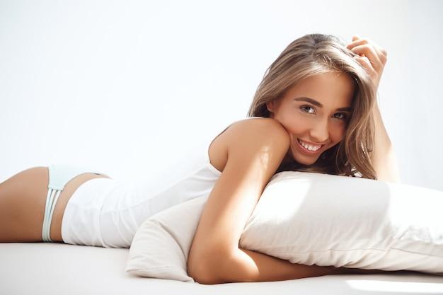Jonge mooie vrouw liggend op bed vroeg in de ochtend