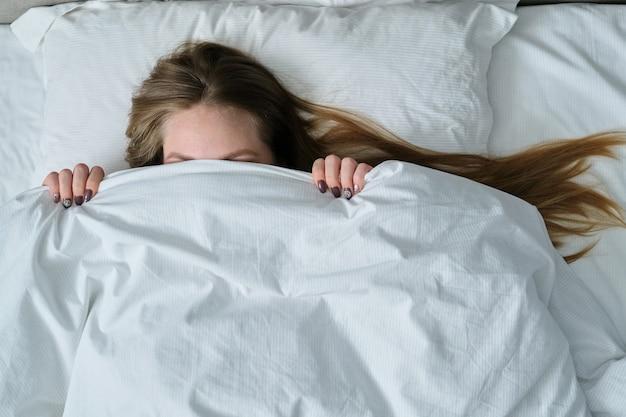 Jonge mooie vrouw liggend op een kussen in bed