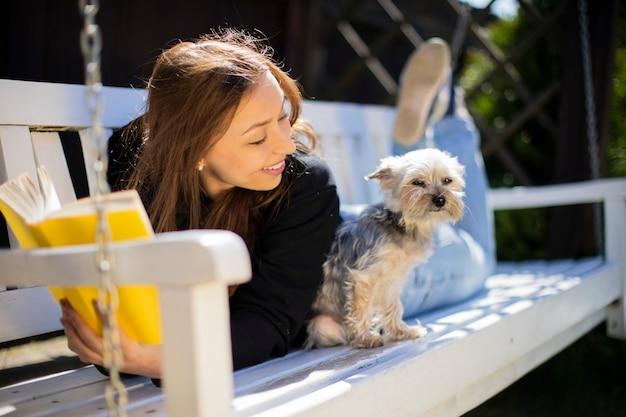 Jonge mooie vrouw liggend op houten schommel in de achtertuin kijkt naar de kleine hond huisdier met glimlach, boek buiten lezen