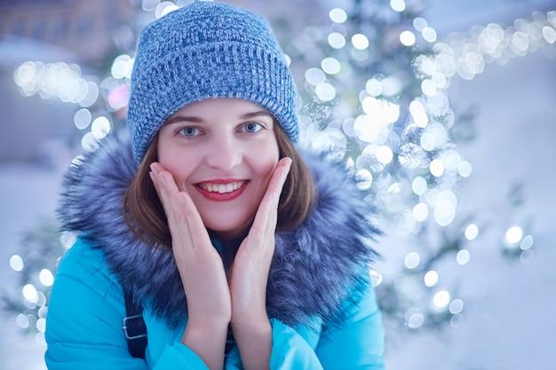 Jonge mooie vrouw loopt op straat, draagt stijlvolle winterkleren, bewondert magische lichten, heeft een blije uitdrukking
