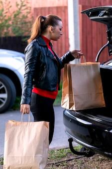 Jonge mooie vrouw lopen naar auto met aankopen bij de supermarkt