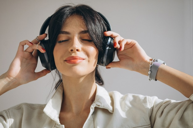 Jonge mooie vrouw luisteren muziek op draadloze koptelefoon