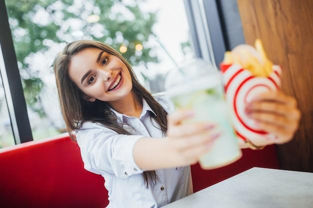 Jonge mooie vrouw lunchen bij fastfood restaurant.