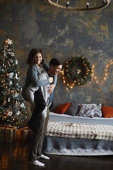 Jonge mooie vrouw maakt grapjes met haar vriendje naast een kerstboom