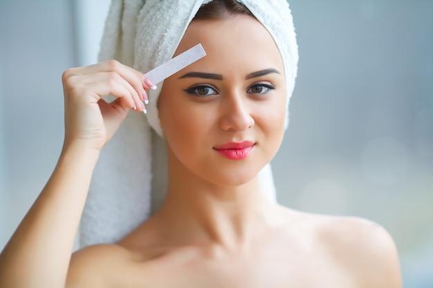 Jonge mooie vrouw maakt wax oogleden in haar badkamer.