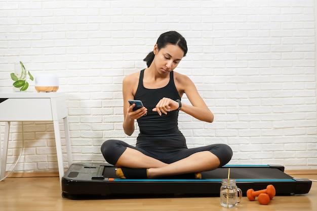Jonge mooie vrouw maatregelen activiteitscontrole met smartphone