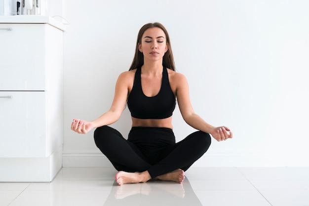 Jonge mooie vrouw mediteren binnenshuis