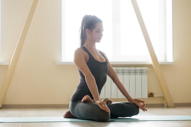 Jonge mooie vrouw mediteren thuis