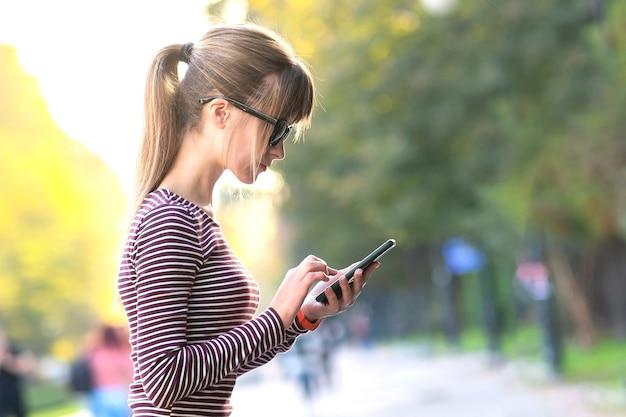 Jonge mooie vrouw messaging op mobiele telefoon op warme herfstdag op een straat in de stad buiten.