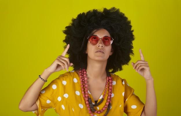 Jonge mooie vrouw met afro krullend kapsel en hartvormige bril op gele achtergrond die omhoog wijst en de richting met vingers aangeeft
