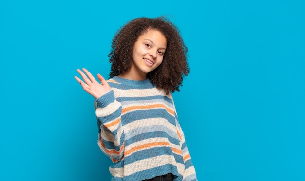 Jonge mooie vrouw met afrohaar en gestreepte trui die zich voordeed op blauwe muur