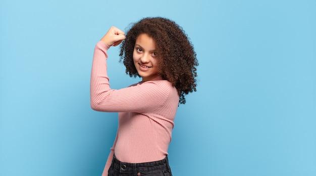 Jonge mooie vrouw met afrohaar en roze trui die zich voordeed op blauwe muur