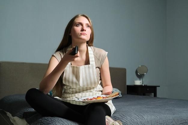 Jonge mooie vrouw met afstandsbediening, ernstige vrouwelijke om thuis te zitten