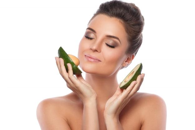 Jonge mooie vrouw met avocadofruit
