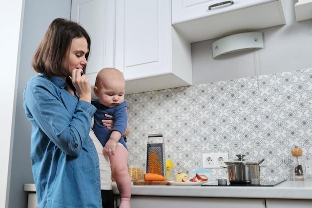 Jonge mooie vrouw met baby in haar armen in de keuken