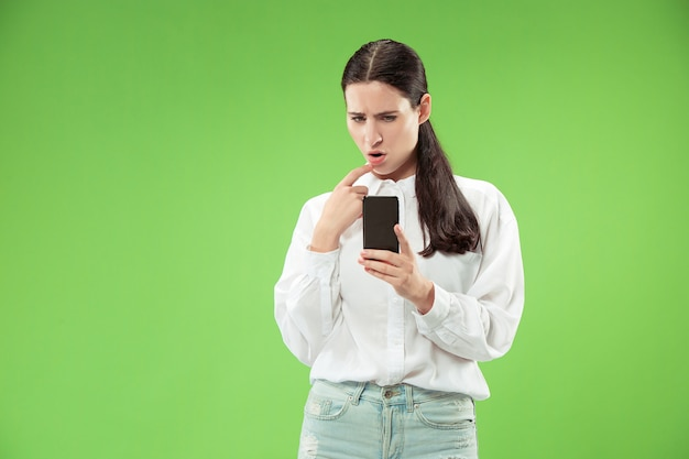 Jonge mooie vrouw met behulp van mobiele telefoon in de studio op groene kleur achtergrond. menselijke gezichtsemoties concept.