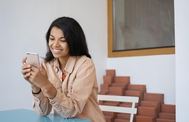 Jonge mooie vrouw met behulp van mobiele telefoon, online winkelen, communicatie, chatten, zittend in café