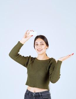 Jonge mooie vrouw met blanco visitekaartje met gelukkige uitdrukking.