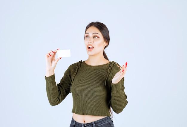 Jonge mooie vrouw met blanco visitekaartje met verbaasde uitdrukking.