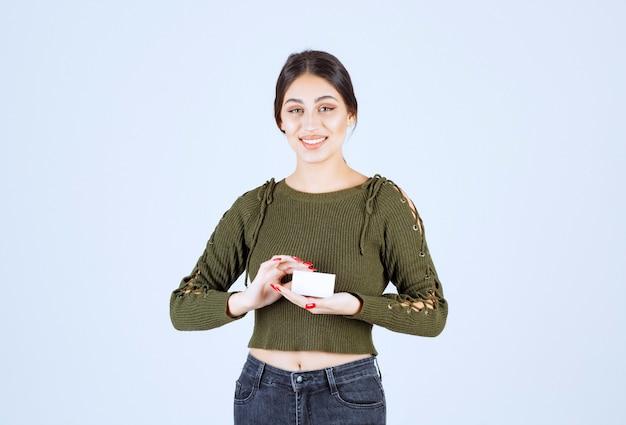 Jonge mooie vrouw met blanco visitekaartje op witte achtergrond.