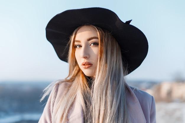 Jonge mooie vrouw met bleke huid met mooie make-up met bruine ogen, met blond haar in een elegante hoed in een roze jas tegen de blauwe lucht. geweldig sensueel meisje.