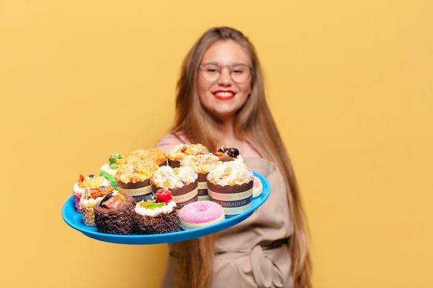 Jonge mooie vrouw met blije en verraste uitdrukking die snoep op een bord houdt
