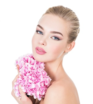 Jonge mooie vrouw met bloemen dichtbij gezicht.