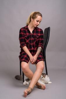 Jonge mooie vrouw met blond haar, gekleed in rood geruit overhemd zittend op een stoel op grijs
