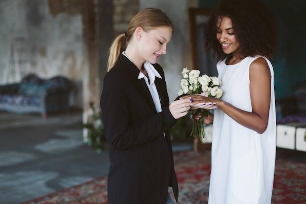 Jonge mooie vrouw met blond haar in zwart pak zetten een trouwring op mooie afrikaanse amerikaanse vrouw met donker krullend haar in witte jurk op huwelijksceremonie