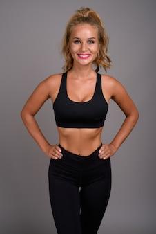 Jonge mooie vrouw met blond haar klaar voor sportschool tegen grijs