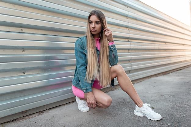 Jonge mooie vrouw met blond lang haar in stijlvolle denim kleding van de zomer in trendy witte sneakers zit in een stad in de buurt van een metalen wand op een zonnige zomerdag. moderne meisje buitenshuis rusten. retro stijl.
