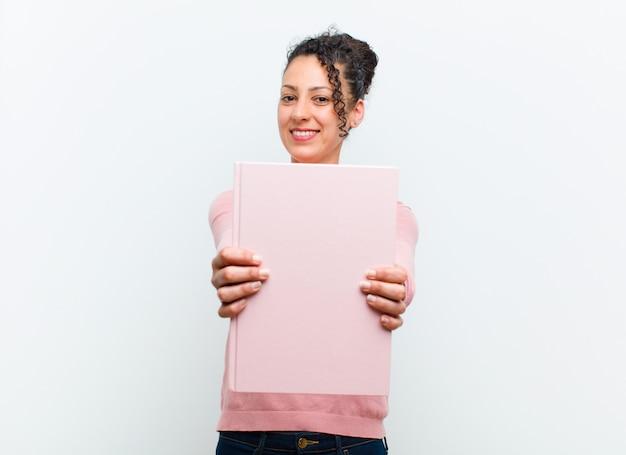 Jonge mooie vrouw met boeken tegen witte muur