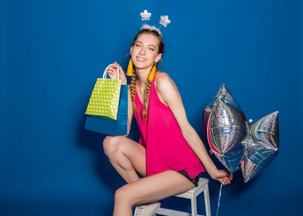 Jonge mooie vrouw met boodschappentassen en ballonnen