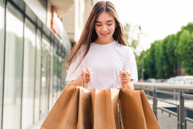 Jonge mooie vrouw met boodschappentassen lopen op de straat in de stad