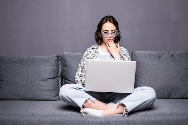 Jonge mooie vrouw met bril met behulp van een laptopcomputer thuis zittend op de bank
