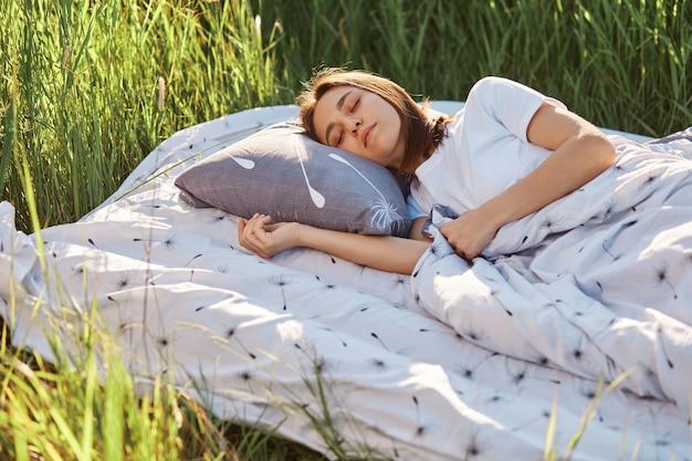 Jonge mooie vrouw met donker haar gekleed wit t-shirt liggend onder deken op zacht bed
