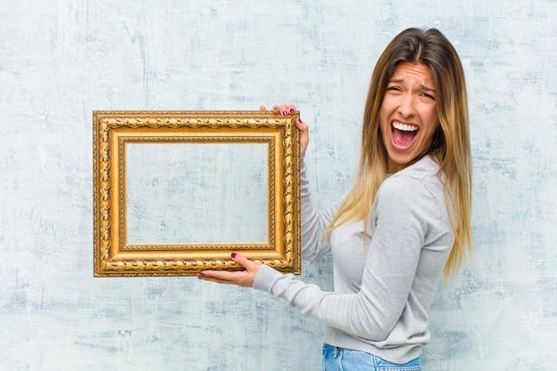 Jonge mooie vrouw met een barok frame tegen grungemuur