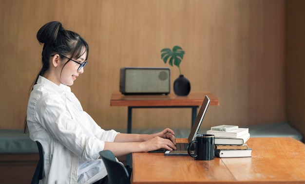 Jonge mooie vrouw met een bril die werkt met tabletcomputer in de woonkamer thuis.