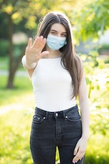 Jonge mooie vrouw met een gezichtsmasker in het park