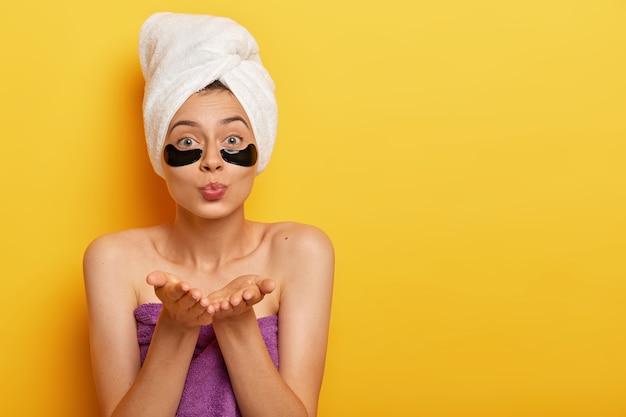 Jonge mooie vrouw met een gezonde huid, houdt de lippen rond, stuurt luchtkus, heeft schoonheidsbehandelingen, voedt de gevoelige huid onder de ogen met patches, heeft blote schouders, geniet van cosmetische behandeling.