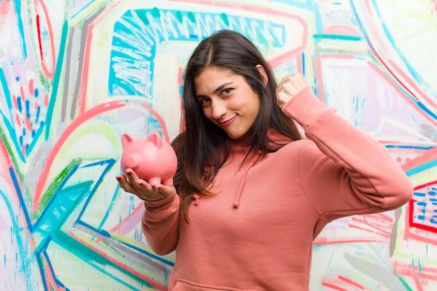 Jonge mooie vrouw met een graffitimuur van het spaarvarken