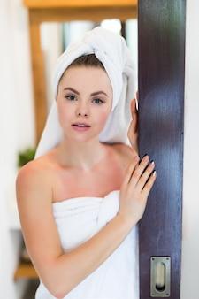 Jonge mooie vrouw met een handdoek op haar hoofd en in een witte jas die zich voorbereiden om een bad te nemen. badprocedures