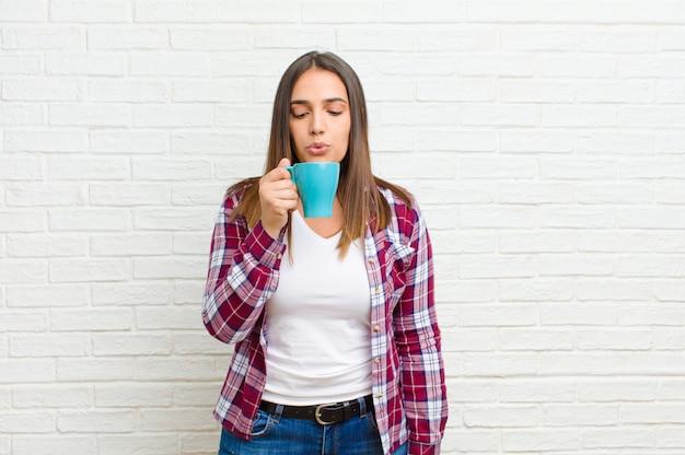 Jonge mooie vrouw met een koffie tegen bakstenen muurtextuur