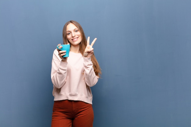 Jonge mooie vrouw met een koffie tegen blauwe muur met een copyspace