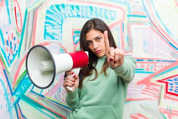 Jonge mooie vrouw met een megafoon tegen graffitimuur
