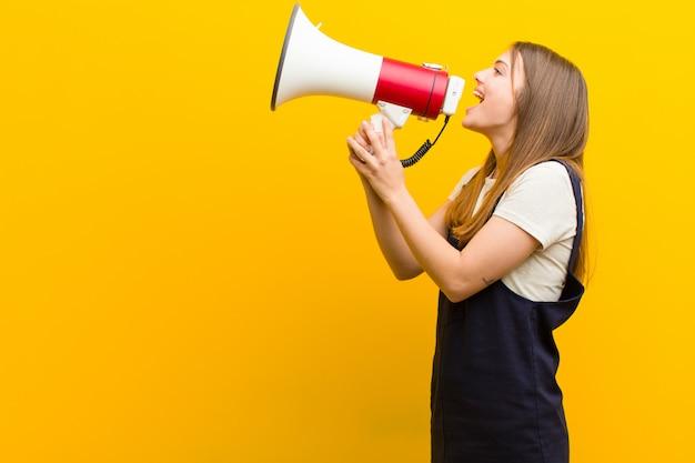 Jonge mooie vrouw met een megafoon tegen oranje achtergrond