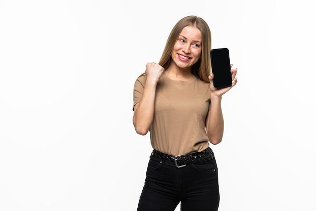 Jonge mooie vrouw met een mobiele telefoon die een overwinning viert