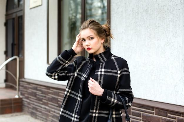 Jonge mooie vrouw met een modieuze tas staat op straat