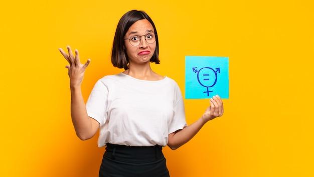Jonge mooie vrouw met een papier met mannelijke en vrouwelijke teken. gelijkheidsconcept